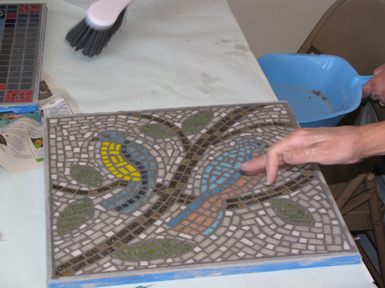 Students working on grouting in tabletop mosaic class